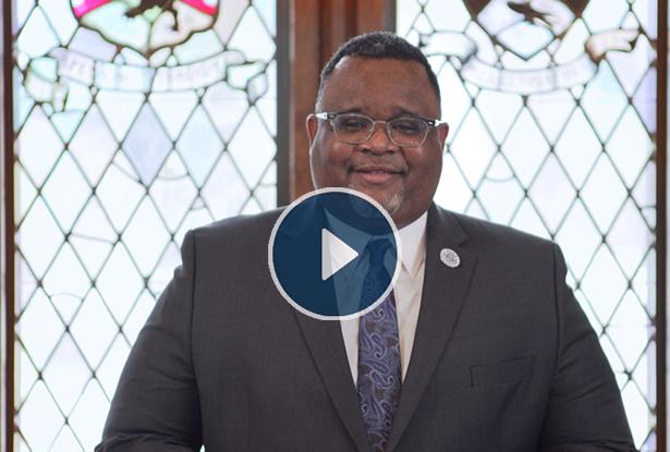 Kean University President Lamont O. Repollet, Ed.D., with a video play button overlay.
