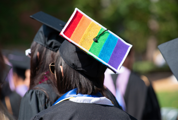A student wears a graduation cap with the LGBTQIA+ rainbow flag on it at commencement