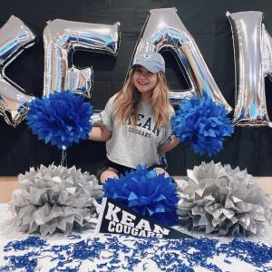 Student poses with pom poms and Kean balloons